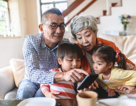 Tech-savvy Chinese grandparents sitting on living room sofa with young grandchildren and using smart phone.